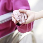 Senior Lady in Wheelchair Holding Hands